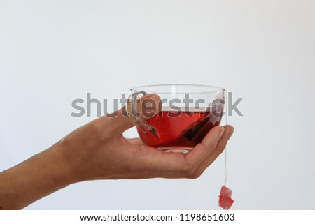 d11fbee3c48c56 Isolated woman hand holding a cup of hot red tea