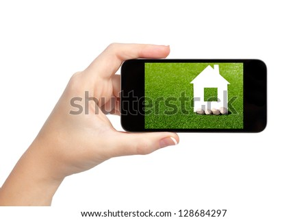 isolated woman hand holding the phone with green grass and a house on the screen