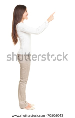 Isolated woman pointing or pushing something with index finger. Beautiful casual young woman isolated on white background in full length standing in profile.