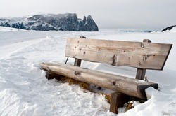 Isolated wooden bench on snow scape in dolomiti, Alps