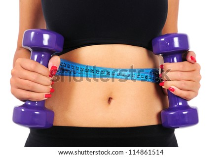 Isolated young fitness woman with dumbbell and measuring tape