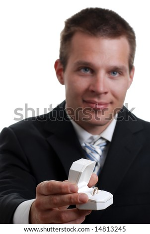 Isolated young man presenting engagement ring on a white background