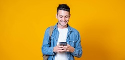 Isolated young man using mobile smart phone on a yellow background - Millennial holding cellphone - People and technology concept