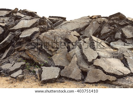 Isolates background ensemble pieces of asphalt road which lay heaped on the ground to be recycled.