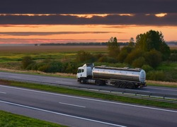 Isothermal Tank truck driving on highway. Oil and Gas Transportation and Logistics. Metal chrome cistern tanker with petrochemicals products. Liquid Chemical Freight. Out of focus