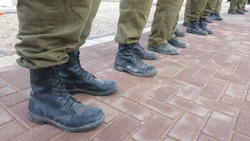 Israel Defense Force reserve duty soldiers standing outside, only their feet seen with military boots. IDF, Israeli soldiers stock image.