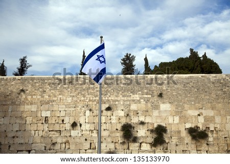 Israel flag fluttering in the wind in front of the holy Wailing Wall, one of the most sacred places to the Jewish people.
