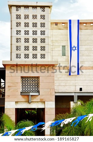 Israel flag in white and blue showing the Star of David hanging vertically on a modern building for Israel\'s Independence Day (Yom Haatzmaut)