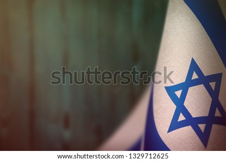Israel hanging flag for honour of veterans day or memorial day on light blue blurred natural wood wall background. Israel glory to the heroes of war concept.
