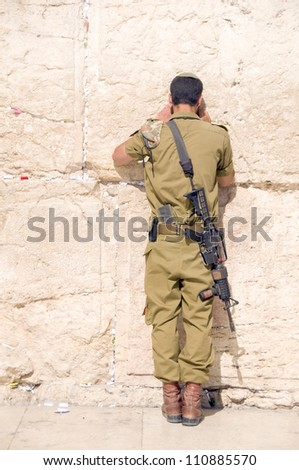 ISRAEL-MAY 28:  Unidentified Israeli military army man prays on May 28, 2012 at The Western Wailing Wall in Jerusalem, Palestine, Israel where people come from all over the world everyday to pray. - stock photo
