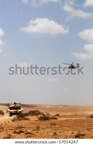 """Israeli Apache hover above a dressed jeep that looks and play as a tank in the national training center in the desert as part of Armour battalion maneuvers. """"Israel 2007""""."""