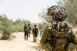Israeli combat soldiers of an elite counter-terror squad return back to base after a raid in South of Lebanon during the Second Lebanon military campaign / war. One soldier is in the foreground.