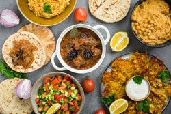 Israeli cuisine: esik fleisch - beef stew with damson plums and spices, hummus,  potato latkes, ptitim, a type of pasta also known as