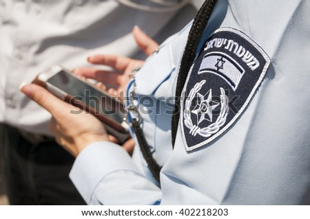 Israeli female police officer with an emblem on her uniform holding cellular phone in her hands. Israeli police concept stock image illustration. Tel Aviv, Israel, April 2014.