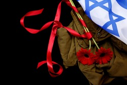 Israeli flag and uniforms with red flowers for the memorial day on black background