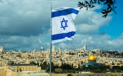 Israeli flag with a Star of David flying over Jerusalem; with Dome of the Rock and the Temple Mount, the rooftops of the Old City and the new city of West Jerusalem skyline in the background
