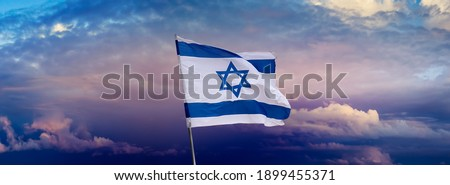 Israeli flag with a star of David over Jerusalem at cloudy sky background on sunset, panoramic view. Patriotic concept about Israel with national state symbols and copy space for wide banner.