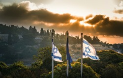 Israeli flags with dramatic stormy sunrise over Mount Zion, Jerusalem, which contains sites that are sacred to Judaism, Christianity and Islam