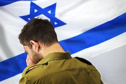 Israeli soldier crying in front of the flag of Israel