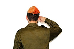 Israeli soldier (Israel Defense Forces, IDF) salutes on white isolated background.  Soldier in army Tzahal uniform with a orange beret on his head. Soldier Israeli Home Front Command