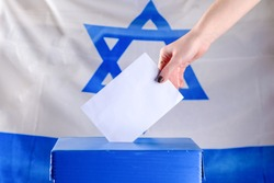 Israeli Young woman putting a ballot in a ballot box on election day. Close up of hand with white votes paper on Israel flag background. Mocup, space for text.