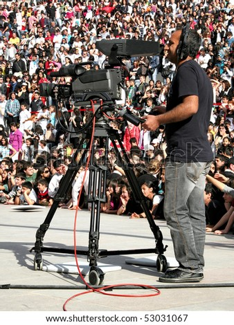 """ISTANBUL - APRIL 25: Cameraman on record during the folk dance show in """"National Sovereignty and Children Day"""" festival at Maltepe University on April 25, 2010 in Istanbul, Turkey."""
