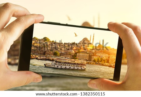 Istanbul at sunset, Turkey. Taking photo of Golden Horn by cell phone. Tourist boat sails in the Istanbul center. Sunny picture of eastern landscape on smartphone. Travel and summer vacation concept.