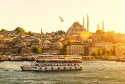 Istanbul at sunset, Turkey. Tourist boat sails on the Golden Horn in summer. Beautiful sunny view of the Istanbul waterfront with a mosque. Concept of nice traveling and vacation in Istanbul.