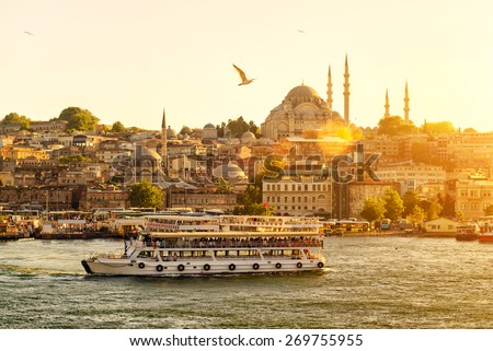 Istanbul at sunset, Turkey. Tourist boat sails on the Golden Horn in summer. Beautiful sunny view of the Istanbul waterfront with a mosque. Concept of traveling and vacation in Istanbul.