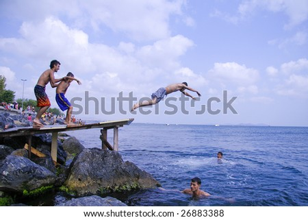 ISTANBUL - AUGUST 5: Teenagers jump into Bosphorus sea from wooden pier in Istanbul, Turkey on August 5, 2007. The Bosphorus is the strait that separates the continents of Europe and Asia.