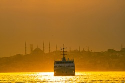 Istanbul inline ferry and cityscape of Istanbul at sunset. Public transportation in Istanbul. Travel to Turkey. Golden hour and ferry on the bosphorus.