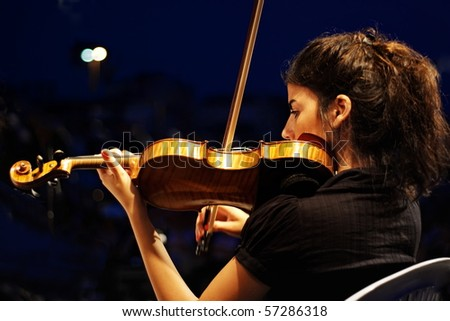 ISTANBUL - JULY 11: Members of the Maltepe Symphonic Orchestra perform live at Maltepe open air stage on July 11, 2010 in Istanbul. Musician playing violin.