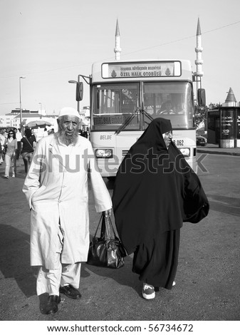 ISTANBUL - JUNE 10: An elderly Muslim couple in traditional black and white garb walk together as they look for their bus stop at Eminonu square on June 10, 2010 in Istanbul.