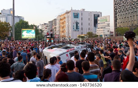 ISTANBUL - JUNE 01: People overturn a policecar in protests on June 01, 2013 in Istanbul, Turkey. Turkish police used disproportionate force to protesters at Taksim in first three days.