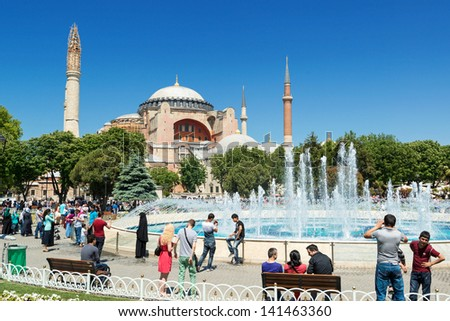 ISTANBUL - MAY 26, 2013: Tourists walk next to Hagia Sophia on may 26, 2013 in Istanbul, Turkey. Hagia Sophia is the greatest monument of Byzantine Culture and tourist attraction.