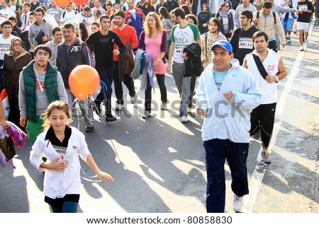 ISTANBUL - OCTOBER 17: An unidentified 12 years old child and a sportsman run during the 32nd Intercontinental Eurasia Marathon run on October 17, 2010 in Istanbul, Turkey.
