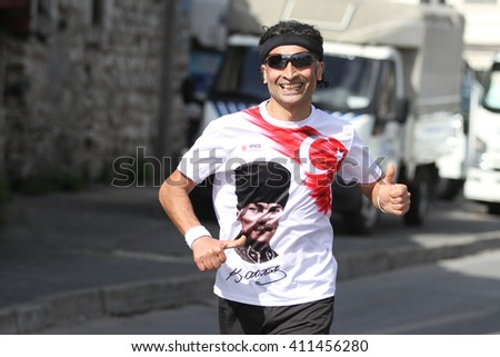 ISTANBUL, TURKEY - APRIL 24, 2016: Athlete is running in Old Town streets of Istanbul during Vodafone Istanbul Half Marathon #411456280