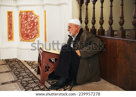 ISTANBUL TURKEY DECEMBER 25 2014 Turkish man reading the Koran at the Ortakoy mosque in istanbul