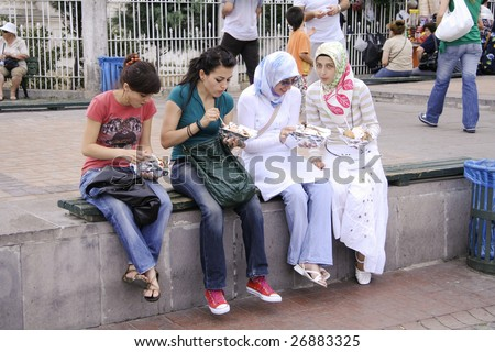 ISTANBUL, TURKEY - JULY 26 : Modern and traditional Turkish girls having take away food in Istabul, Turkey on July 26, 2007. Islam is the largest community follows by Christians, Catholics and Jews.