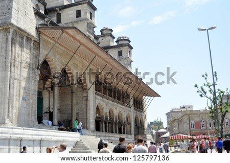 ISTANBUL, TURKEY - JUNE 03: Tourists near Valide Sultan Mosque on June 03, 2012 in Istanbul, Turkey. Valide Sultan Mosque is most famous as Yeni Cami and was built during 1597-1663 by Ottoman.