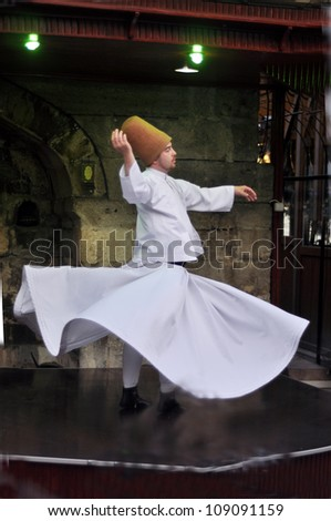 ISTANBUL, TURKEY - JUNE 03: Whirling dervish dancing in Cafe Mesale on June 03, 2012 in Istanbul, Turkey. Sufi whirling is a form of Sama or physically active meditation practiced by Sufi Dervishes.