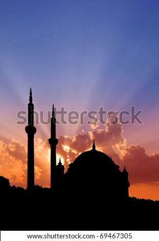 Istanbul Turkish mosque outlined by sunset showing dome and minarets.