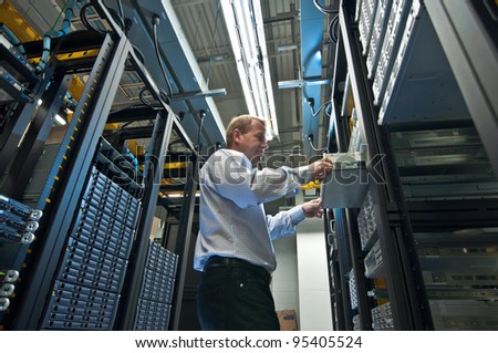 IT administrator installing a new rack mount server. Large scale storage server is also seen.