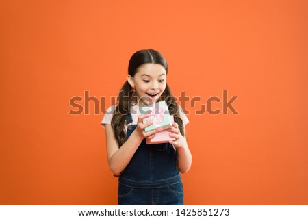 It caught her by surprise. Cute small child opening gift box with surprise face on orange background. Adorable little girl getting birthday surprise. Being shocked of pleasant surprise. #1425851273