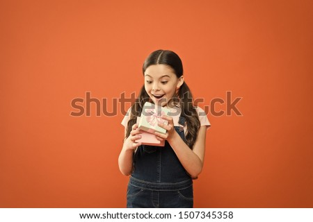 It caught her by surprise. Cute small child opening gift box with surprise face on orange background. Adorable little girl getting birthday surprise. Being shocked of pleasant surprise.
