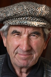 It depicts an elderly, smiling man in a cap