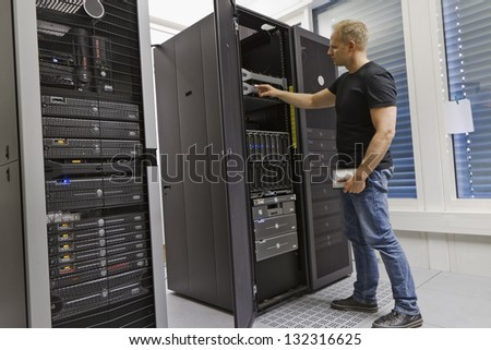 It engineer / consultant working in a data center. Holding a hard drive and opning a server.