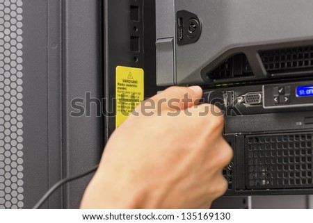 It engineer / consultant working in a data center. Plugs in a usb cable.