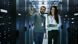 IT Engineer Shows Working Data Center / Server Room to Female Chief Engineer who Holds Tablet Computer.