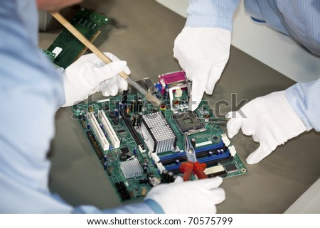 IT engineers doing cleaning and repairs on a motherboard